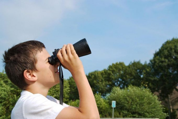Kid uses binoculars