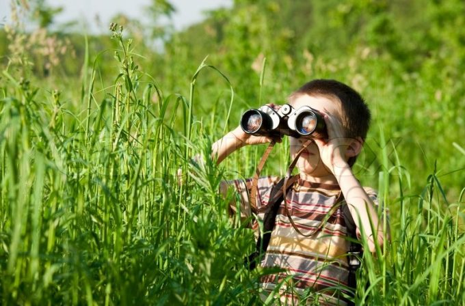 Kid watches with binoculars