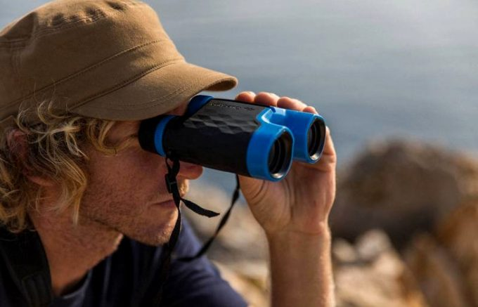 Using binoculars atop a mountain