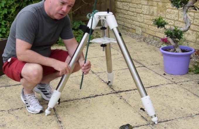 man setting up telescope tripod
