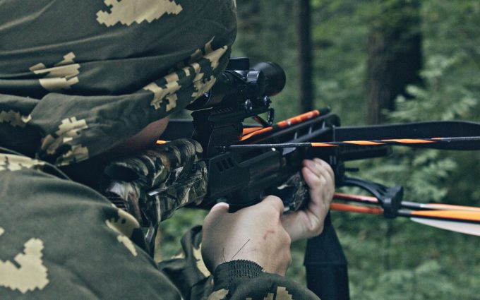 A man shooting his crossbow through a scope