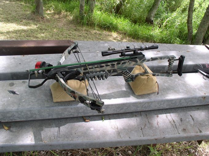 A crossbow with a scope ready for use on the table