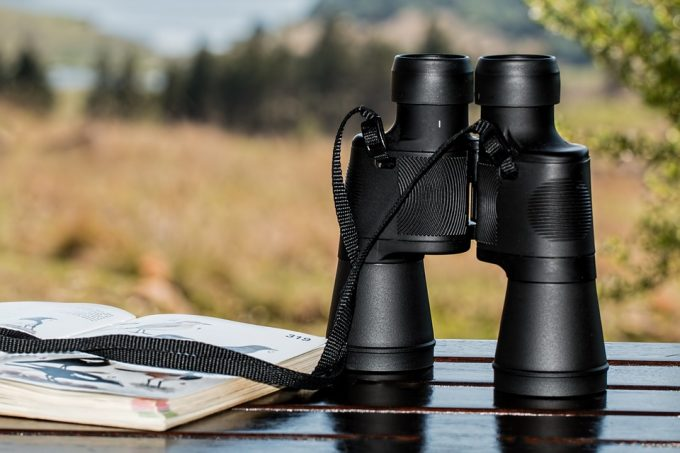 binoculars on table next to a book